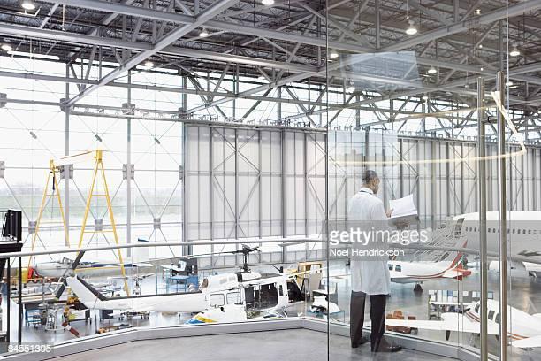 man in lab coat in aircraft hangar - luftfahrzeug stock-fotos und bilder