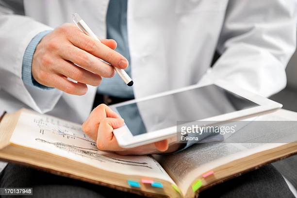 Man in lab coat using digital tablet and open book