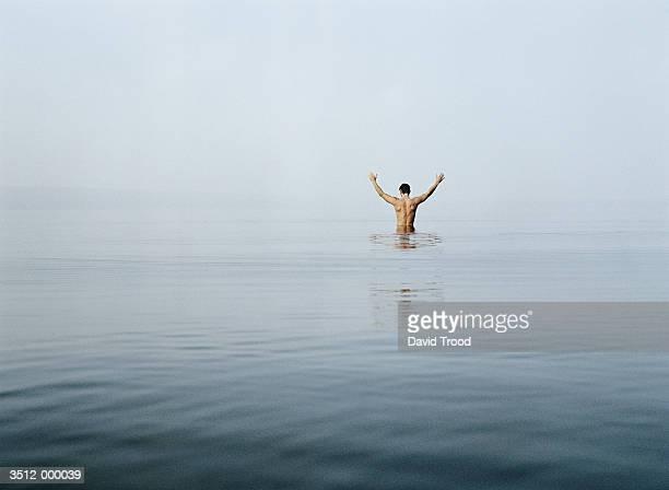 Man in Lake Raises Arms