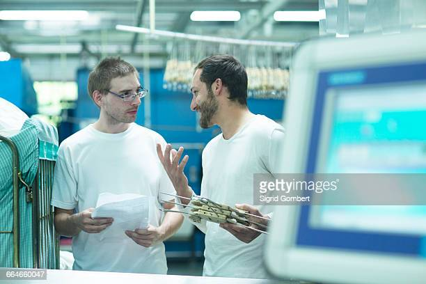 man in launderette holding coat hangers talking to colleague - sigrid gombert stock pictures, royalty-free photos & images