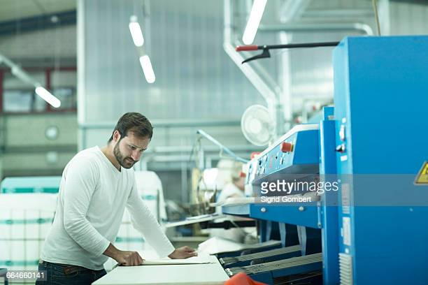 man in launderette using laundry folding machine - sigrid gombert stock pictures, royalty-free photos & images