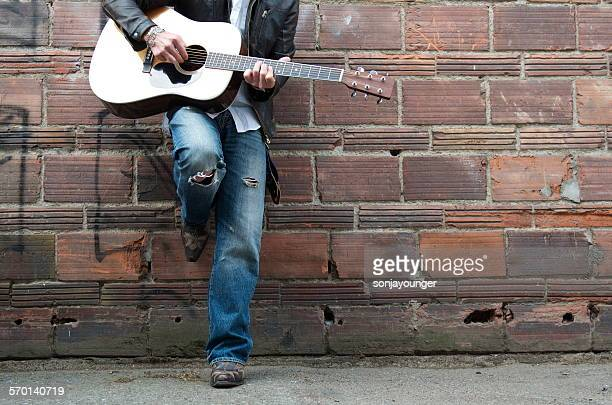 Man in Leather Jacket and Cowboy Boots Playing the Guitar in an Alley