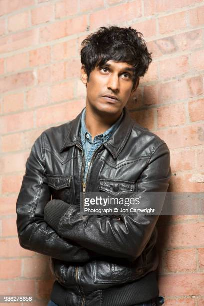 Man in leather jacket leans coolly against a wall