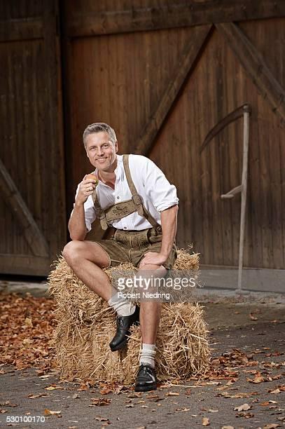 Man in lederhosen on farm, Barvaria, Germany