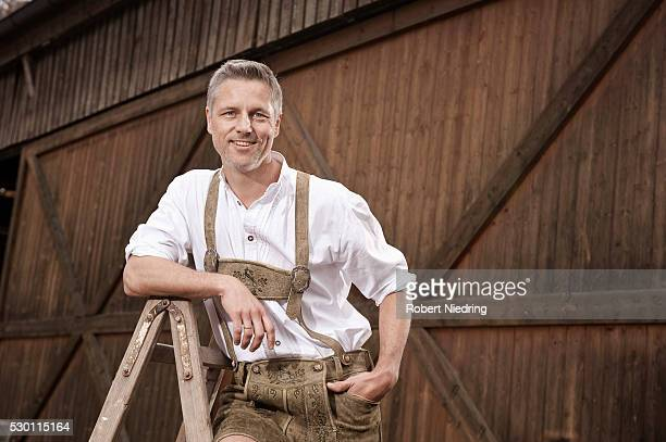 Man in lederhosen on farm, Barvaria, Germany