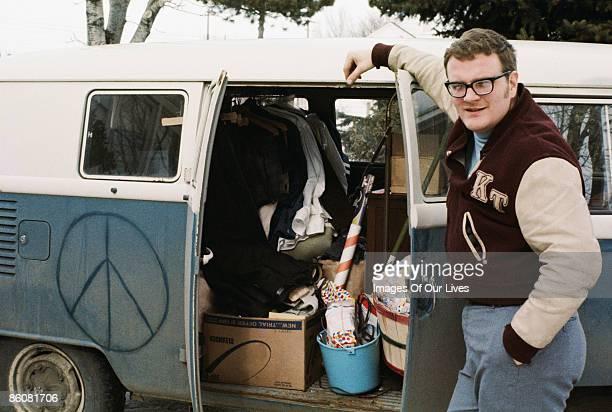 Man in letterman jacket by messy van