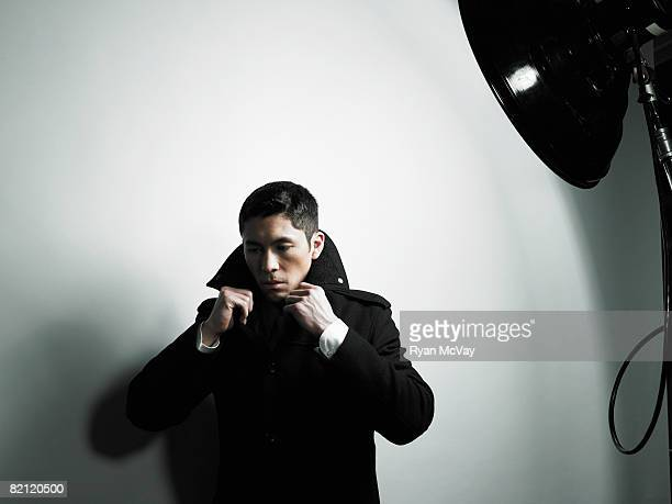 man in light, lifting up collar - overcoat stock pictures, royalty-free photos & images