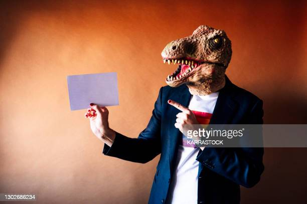 man in lizard mask holding a white sign - bear suit stock pictures, royalty-free photos & images