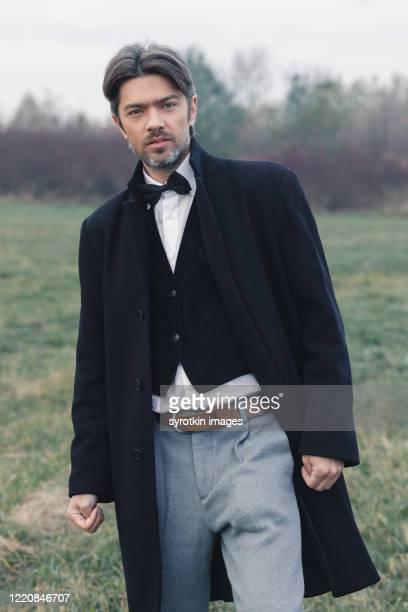 man in long black coat looking at camera - ビクトリア様式 ストックフォトと画像