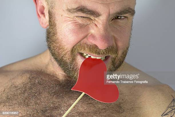 man in love bites a heart - hairy man chest stock pictures, royalty-free photos & images
