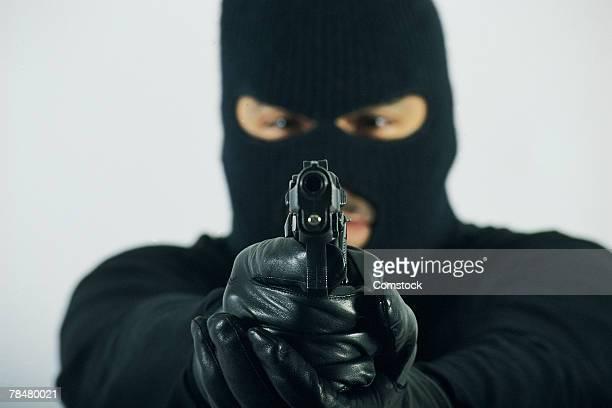 Man in mask aiming gun