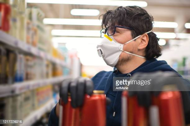 man in mask and rubber gloves choosing a drink in a supermarket - corona beer stock pictures, royalty-free photos & images