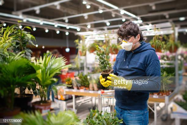 man in mask and rubber gloves choosing a plant in a garden center - illness prevention stock pictures, royalty-free photos & images