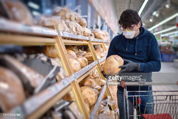 man in mask and rubber gloves choosing bread in a supermarket - illness prevention stock pictures, royalty-free photos & images