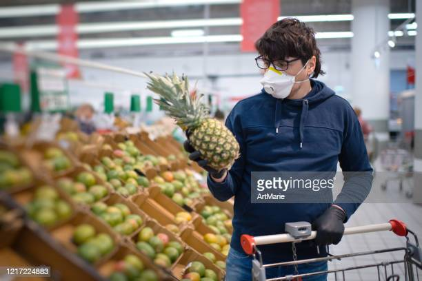 man in mask and rubber gloves choosing pineapple in a supermarket - n95 respirator mask stock pictures, royalty-free photos & images