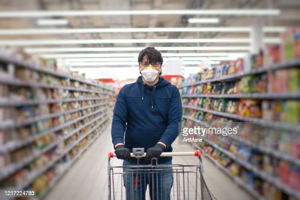 man in mask and rubber gloves in a supermarket - n95 respirator mask stock pictures, royalty-free photos & images