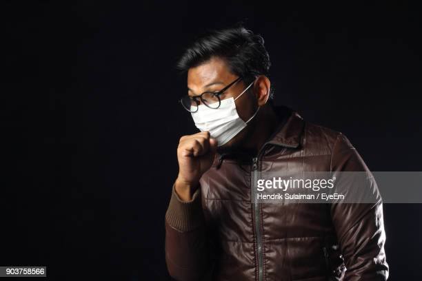 man in mask coughing while standing against black background - black mask disguise stock pictures, royalty-free photos & images