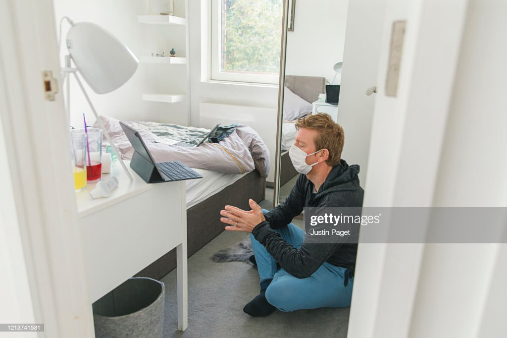 Man in mask meditating in bedroom : Stock Photo