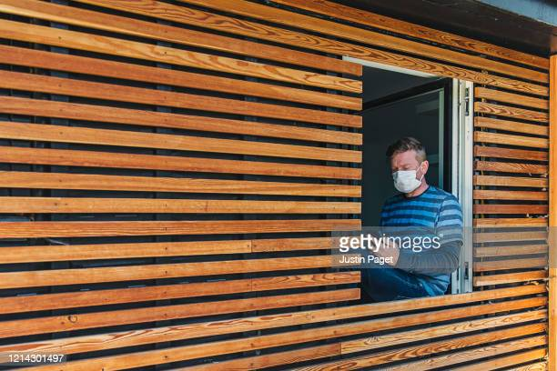man in mask sitting in window of modern house - orange stock pictures, royalty-free photos & images