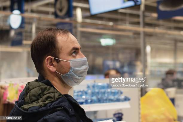 man in medical face mask looks up. shopping in the store before lockdown or during quarantine. - ニジニ・ノヴゴロド州 ストックフォトと画像