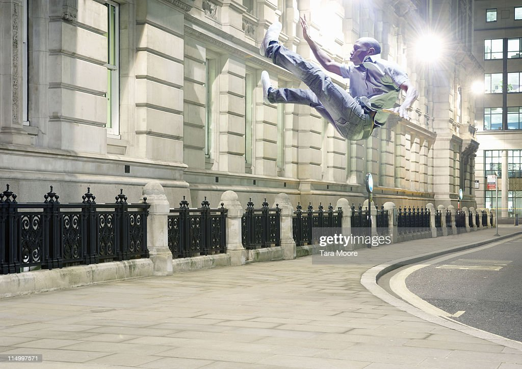 man in mid air in city : Stock Photo