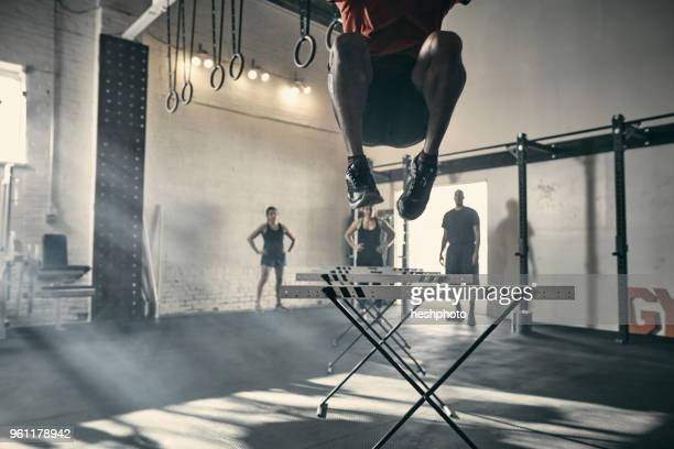 man in mid air jumping hurdles in gym - heshphoto stock pictures, royalty-free photos & images
