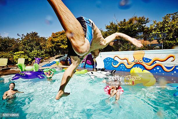 man in mid air jumping into pool during party - pool party stock pictures, royalty-free photos & images