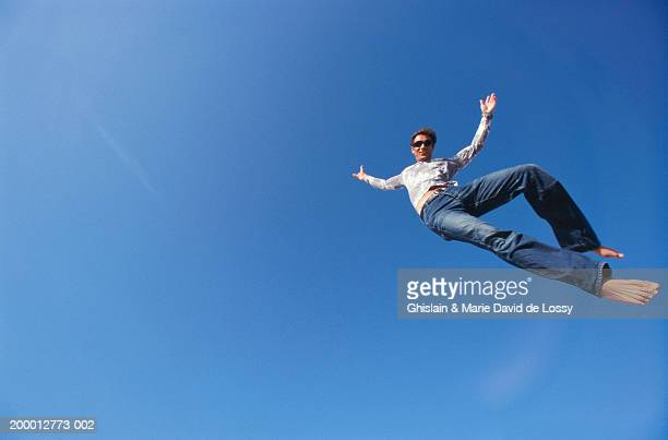 man in mid-air against blue sky, portrait (wide angle) - wide angle stock pictures, royalty-free photos & images