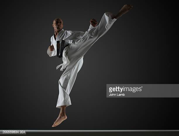 man in mid-air performing karate kick - martial arts stock pictures, royalty-free photos & images