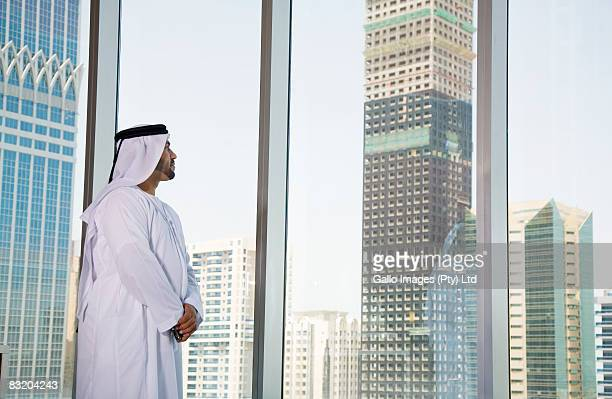 Man in Middle Eastern traditional dress looking out at Dubai cityscape, UAE