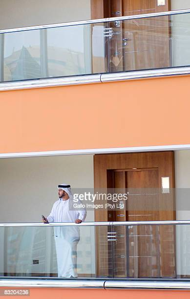 Man in Middle Eastern traditional dress standing at balcony, Dubai, UAE