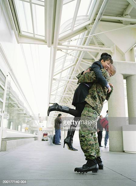 Man in military uniform lifting woman up in airport