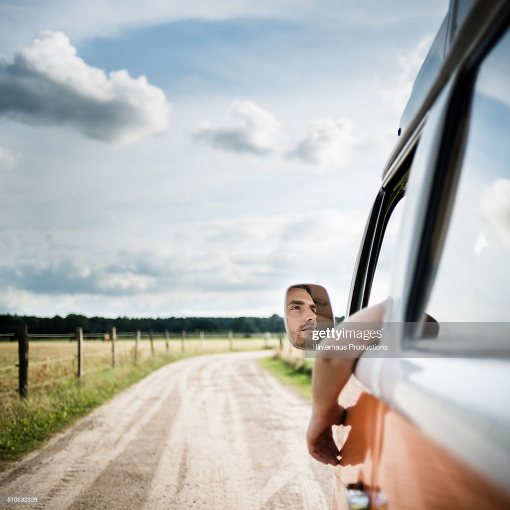 Man In Mirror Of A Bus On Country Road : Stock Photo