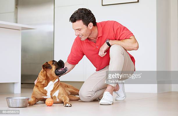 Man in modern house petting dog on the floor