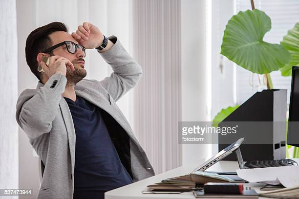 Man in modern office talking on mobile phone