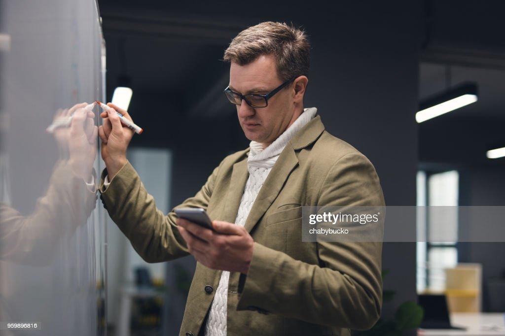 Mann in modernen Büro an die Tafel schreiben : Stock-Foto