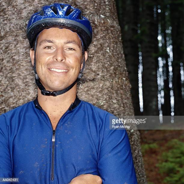 Man in mountain biking gear, leaning against tree, portrait