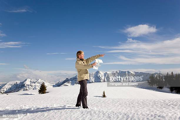 man in mountains pointing with map