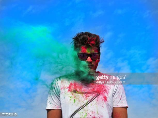 Man In Multi Colored Smoke Against Blue Sky