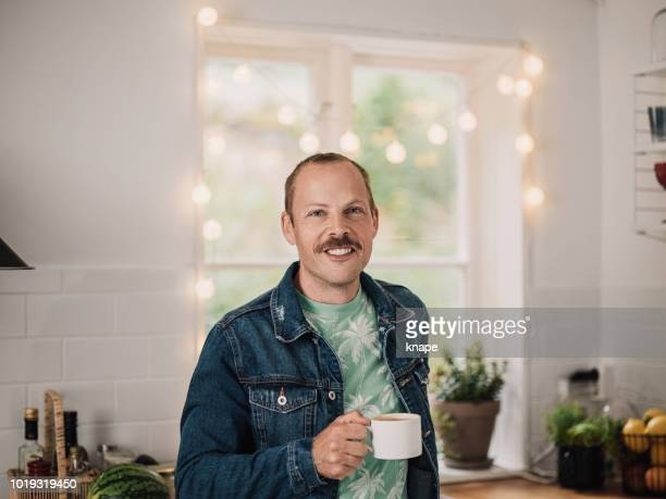Man in mustasch in his kitchen at home