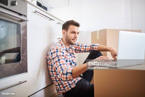 man in new apartment - surfing the net stock photos and pictures