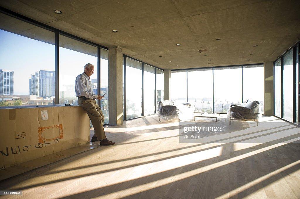 man in new condo checking phone : Stock-Foto