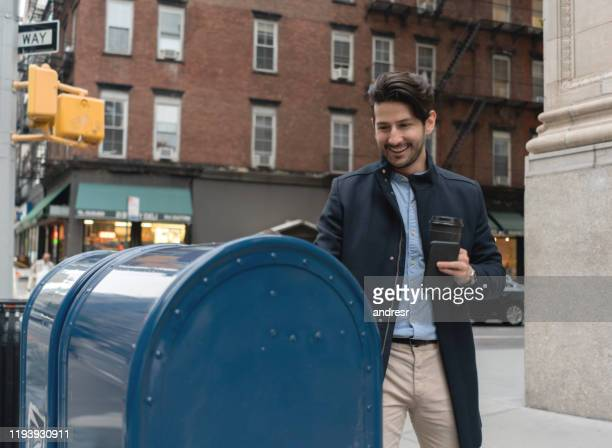 man in new york putting a letter in the mail - sending stock pictures, royalty-free photos & images
