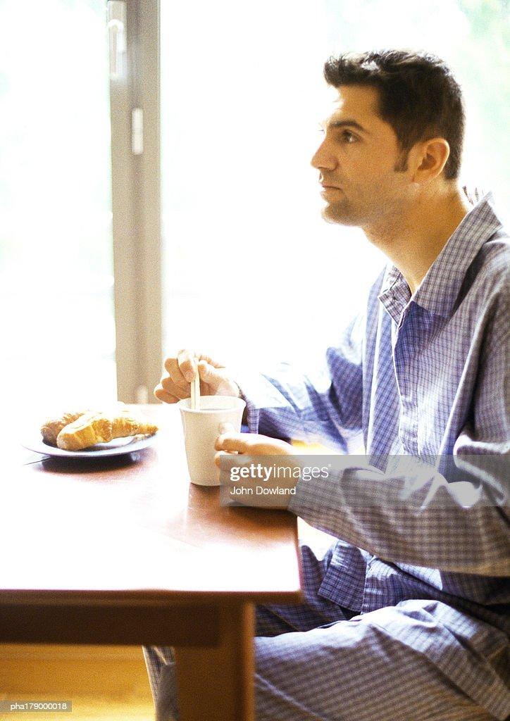 Man in nightshirt having breakfast : Stockfoto