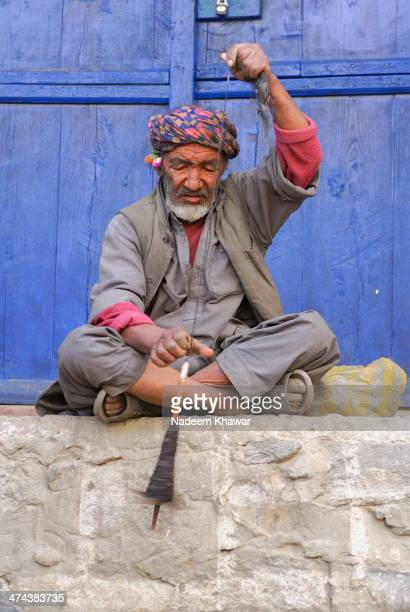 Man in Northern areas of Pakistan near Hoshe valley spinning the thread with ancient and traditional style with the hair of yaks.