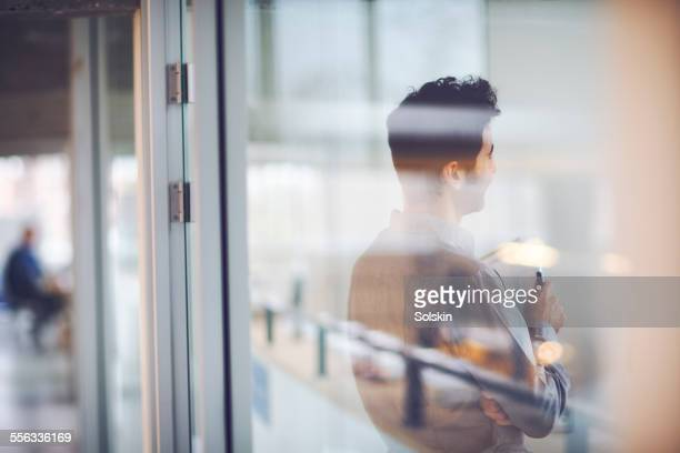 man in office behind glass wall
