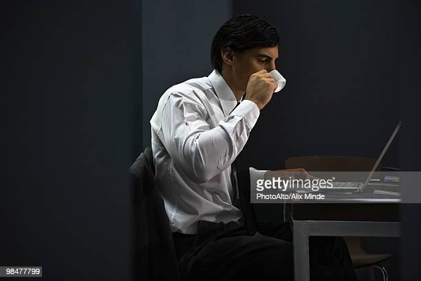 Man in office drinking coffee, working late