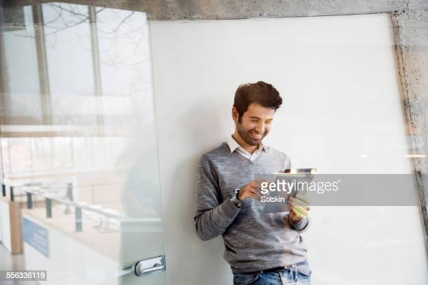 Man in office looking af tablet computer