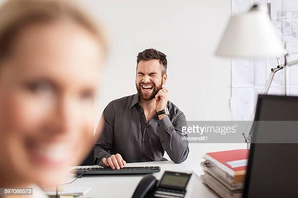 man in office screaming at desk with woman in foreground - scham stock-fotos und bilder