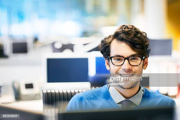 Man in office smiling to camera